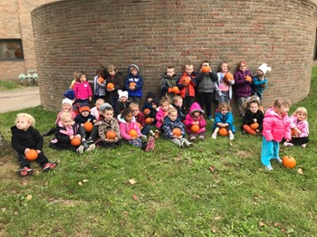 This is a picture of preschool students holding pumpkins.