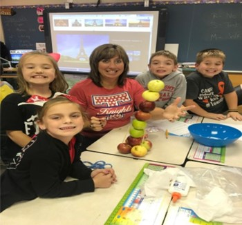 This is a picture of a second grade teacher with her students.
