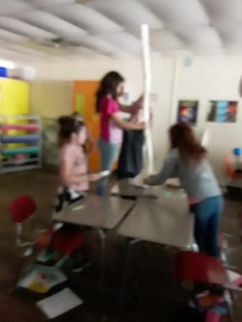 This is a picture of 5th grade students building towers in class out of paper.